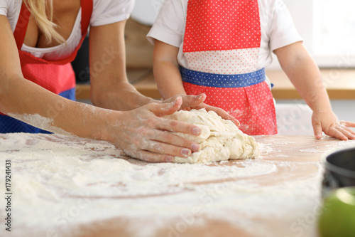 Mother and her cute daughter hands prepares the dough on wooden table. Homemade pastry for bread or pizza. Bakery background