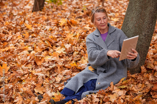 Poster Oranje eclat The adult woman touches the tablet with her finger. Sits under a tree in a park in the fall.