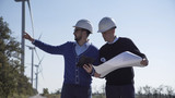 Two engineers discussing a blueprint on a wind farm in front of a turbine supplying alternative electricity from the conversion of kinetic energy - 179250472