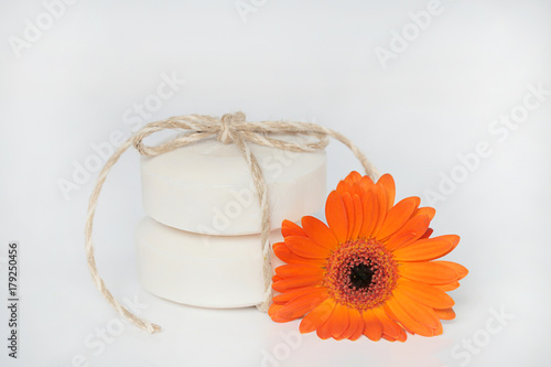 Fotobehang Gerbera flower soap. two white round soap and a orange gerbera flower on a light background. Handmade soap