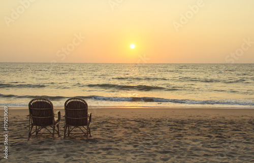 Foto op Aluminium Strand Two chairs near coastline at sunset time