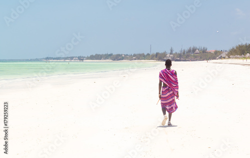 Foto op Plexiglas Zanzibar Unrecognizable Maasai warrior walking on picture perfect tropical sandy beach of Paje, on Zanzibar island, Tanzania, East Africa.