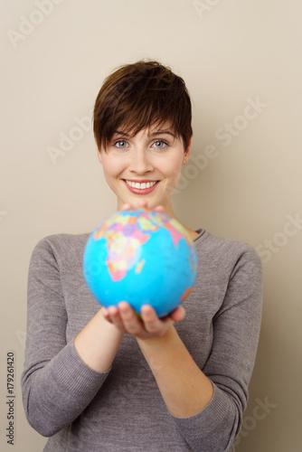 Foto Murales lachende frau zeigt eine weltkugel mit beiden händen