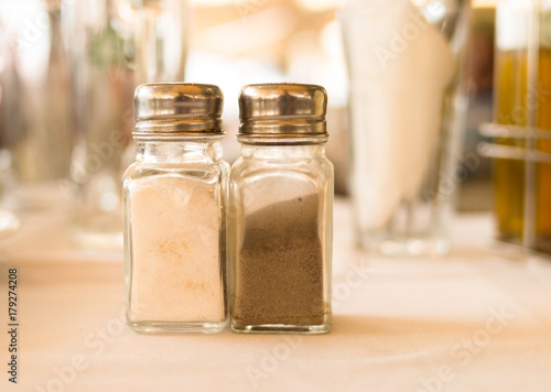 Foto op Canvas Pizzeria salt pepper traditional seasoning in transparent glass vessels with chrome top on a blurred background