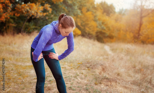 Exhausted caucasian jogger girl  resting after jogging on the autumnal forest hill. - 179274294