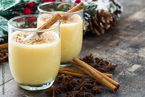 Poster Homemade eggnog with cinnamon on wooden table. Typical Christmas dessert.Copyspace