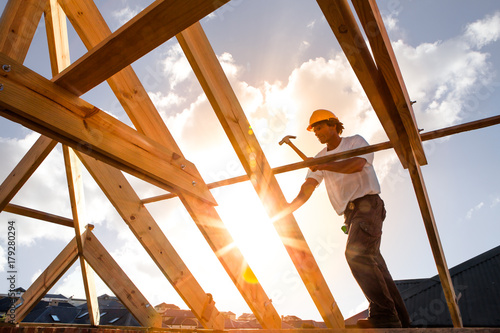 roofer ,carpenter working on roof structure at construction site - 179280294