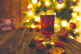 Hot mulled wine with spices and Christmas tree on wooden background. Christmas or New Year concept - 179281688