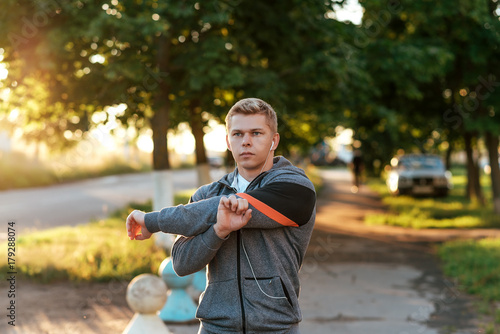 A male coach kneads his hands before training in headphones. Runner in the morning in park. Listens to music, confident look. Summer lifestyle, motivation is strong. Outdoors in the city.