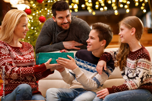 Christmas family together, son give gift to mother