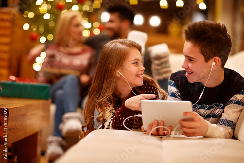 Girl and boy listening music on tablet together