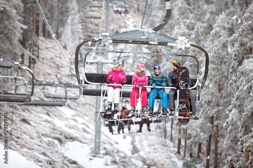 Family together in ski chair going to ski terrain