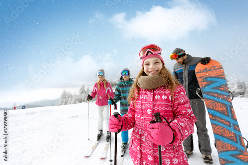 Smiling girl with family on ski terrain