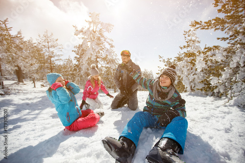 Family having fun on snow in mountain at winter