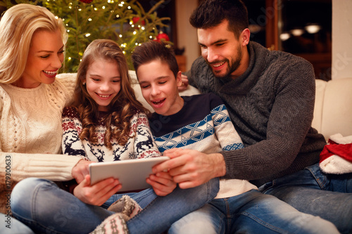 Family gathered around a Christmas tree and using tablet.