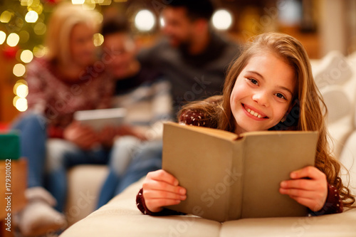 little girl lying and reading children book for Christmas.