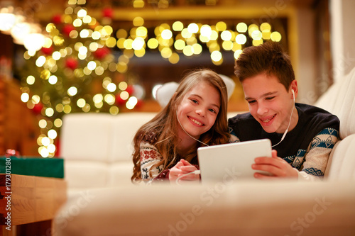 boy and girl with headphones lying and using a tablet for Christmas.