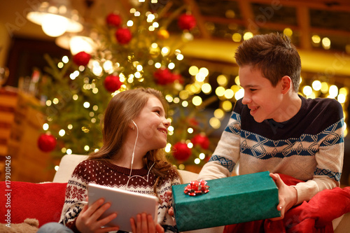 older brother surprise with present his little sister on Christmas .