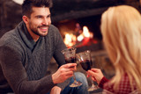 romantic couple sitting on floor at burning fireplace and drink wine. - 179301679