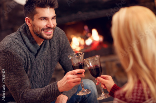 romantic couple sitting on floor at burning fireplace and drink wine.
