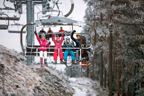Ski lift transports family skiers and snowboarders at snowy mountain