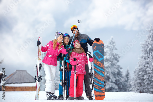 Skiing family enjoying winter vacation on snow in cold day and making mobile selfie