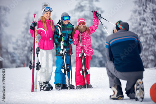 Ski, snow sun and fun - father taking picture of family on snow