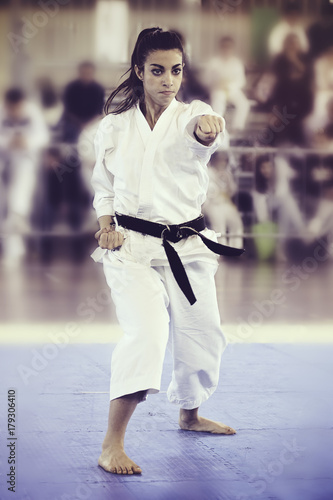 A black belt girl is performing a kata at a karate competition Poster