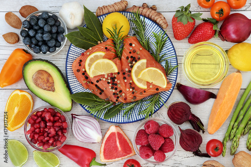 Nutrition for a healthy heart concept with fresh salmon, fruit, vegetables, nuts, herbs, spice and olive oil. Food very high in omega 3 fatty acids, antioxidants, anthocyanins, mineral and vitamins. © marilyn barbone