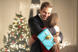 Handsome guy hugging her girlfriend and thanks her for her Christmas gift