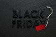 Black Friday text with red sale tag on slate background