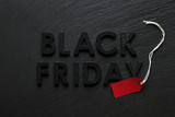 Black Friday text with red sale tag on slate background - 179328091