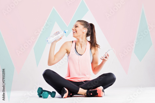Fototapeta Fitness young woman drinking water and holding smart phone