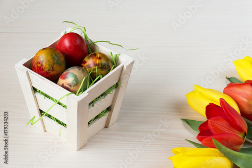 Easter wicker basket with colored eggs and yellow and red tulips on white wooden board.