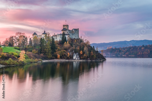 Wonderful castle by the lake at dusk in autumn