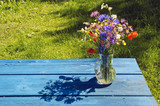 summer wild flowers bouquet in glass vase on blue table