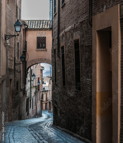 Foto op Canvas Smal steegje A narrow street with an arch connecting two opposite buildings. The street runs downwards opening a view to thw mountains. Invitation to travel