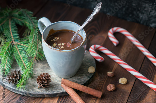 Foto op Canvas Chocolade Cup of hot chocolate with hazelnuts and cinnamon sticks on wooden table. Sweet candy canes, fir branches and cones decoration. Christmas holiday background.