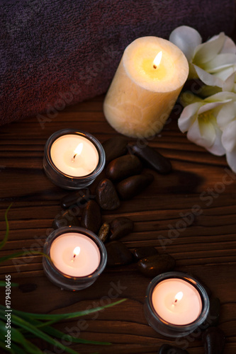 A candle in a glass vase, decoration and various interesting elements on a dark wooden background. Candles burning. Set for spa and massage. stones for massage © Роксолана Осыка