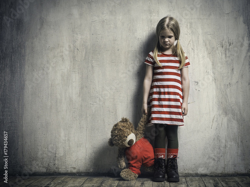 Sad girl with a toy bear on a background of textured walls. The concept of children's resentment, the complexity of education, the child's behavior