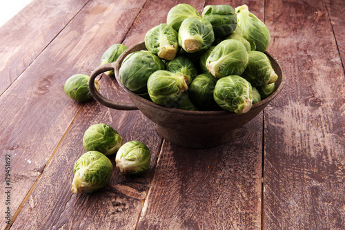 Fotobehang Brussel Fresh brussel sprouts over rustic wooden texture and in a vintage bowl.