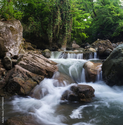 A small waterfall among the rocks on the mountain river - 179464430