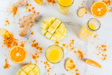 Indian cuisine recipes. Healthy food, detox water. Traditional Indian mango, orange, turmeric and ginger smoothie, on a white marble table. Copy space top view - 179465629