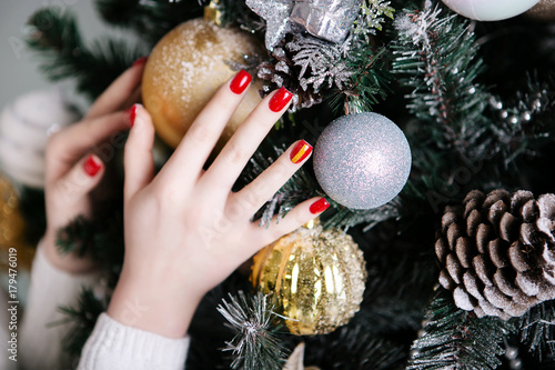 Staande foto Manicure Manicure for the New Year in red against the background of Christmas trees and Christmas toys