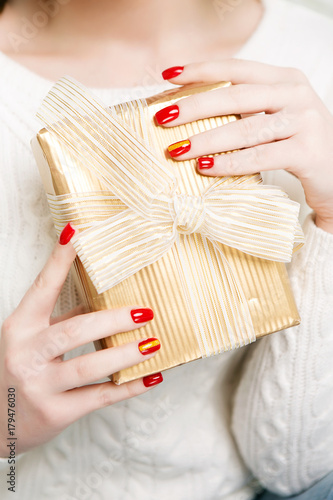 Foto op Plexiglas Manicure Christmas manicure red close-up. Neil art for the holiday. Beautiful hands holding a gift box.
