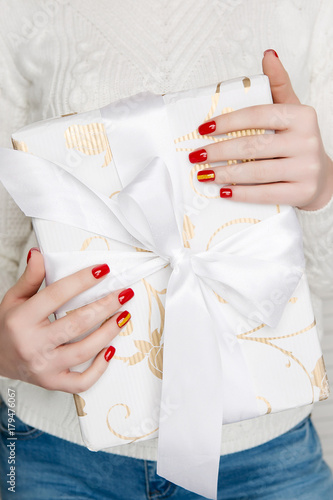 Aluminium Manicure Red Christmas manicure with gold strip. The girl is holding a New Year gift.