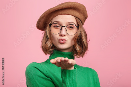 Papiers peints Salon de coiffure Studio shot of attractive gorgeous woman in spectacles blows sweet kiss at camera, flirts with boyfriend, says goodbye. Adorable female sends kiss to you. People, farewell, relationship concept