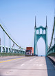 Red big rig semi truck carry container on flat bed trailer and moving on gothic arched St Johns bridge in Portland