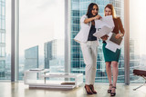 Female businesswomen wearing formal outfit discussing documents standing in office hallway