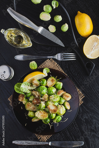 In de dag Brussel Roasted Brussel Sprouts with Parmesan cheese, lemon, Salt, Pepper on a black table. top view